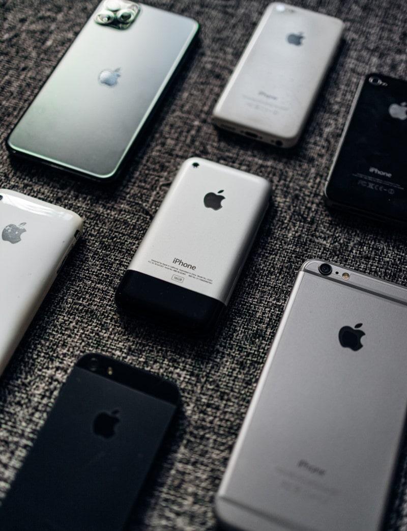 Παλιά και νέα μοντέλα iPhone επάνω σε τραπέζι με το πίσω μέρος προς τα πάνω