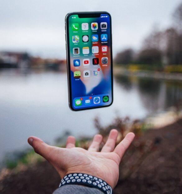 Συσκευή iPhone στον αέρα με φόντο μια λίμνη