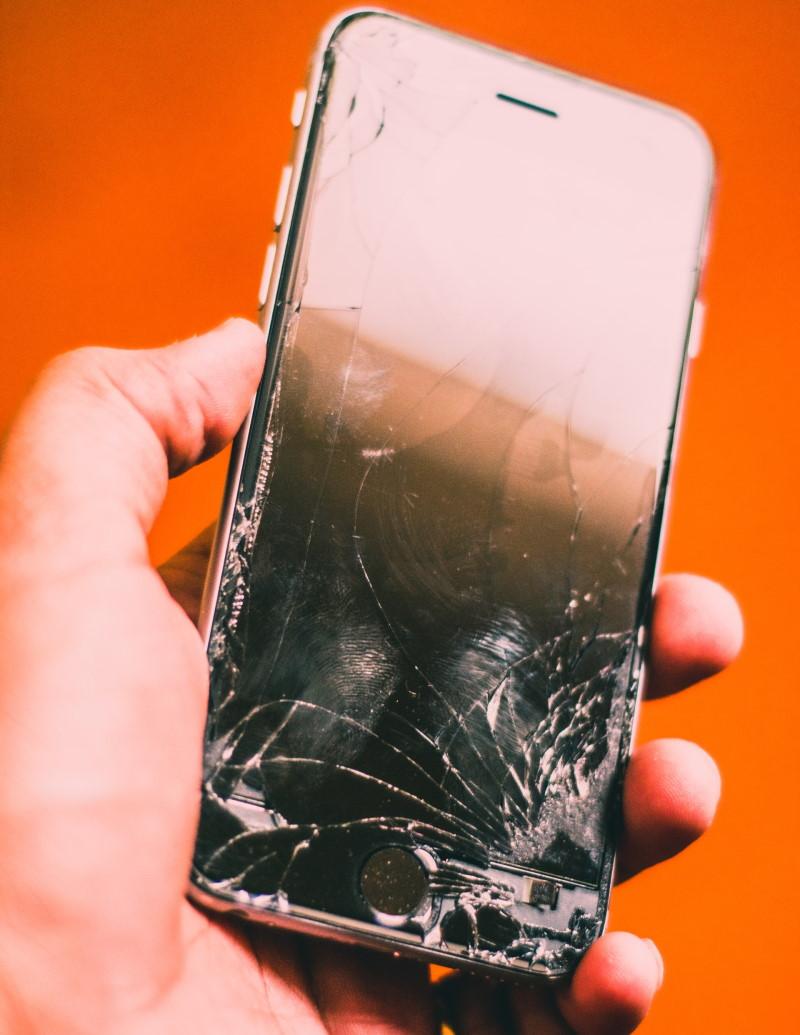 Χέρι κρατάει iPhone με σπασμένη οθόνη