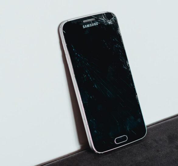 Smartphone Samsung με σπασμένη οθόνη δίπλα σε λευκό τοίχο