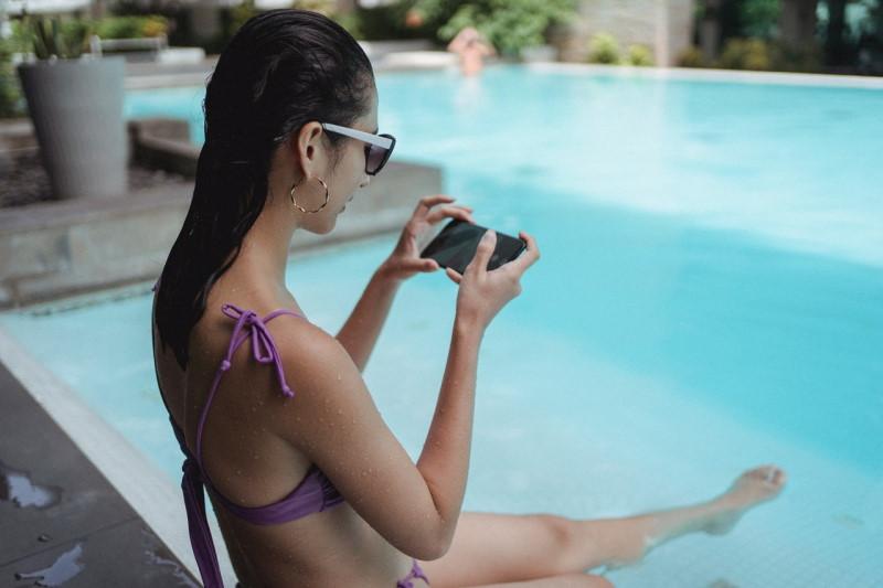 Γυναίκα χρησιμοποιεί κινητό δίπλα σε πισίνα