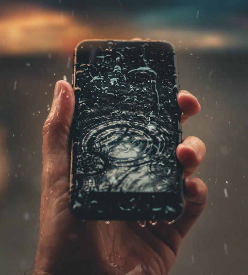 Ανδρικό χέρι κρατάει κινητό στη βροχή