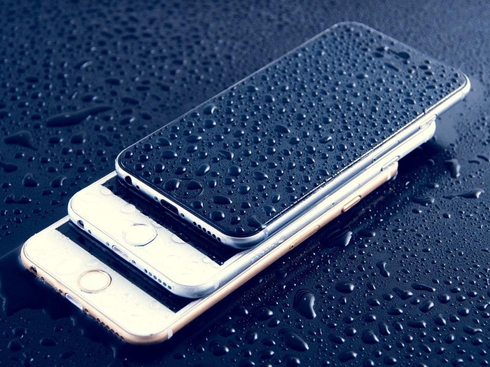 Τρία βρεγμένα με νερό iPhones επάνω σε μαύρο τραπέζι